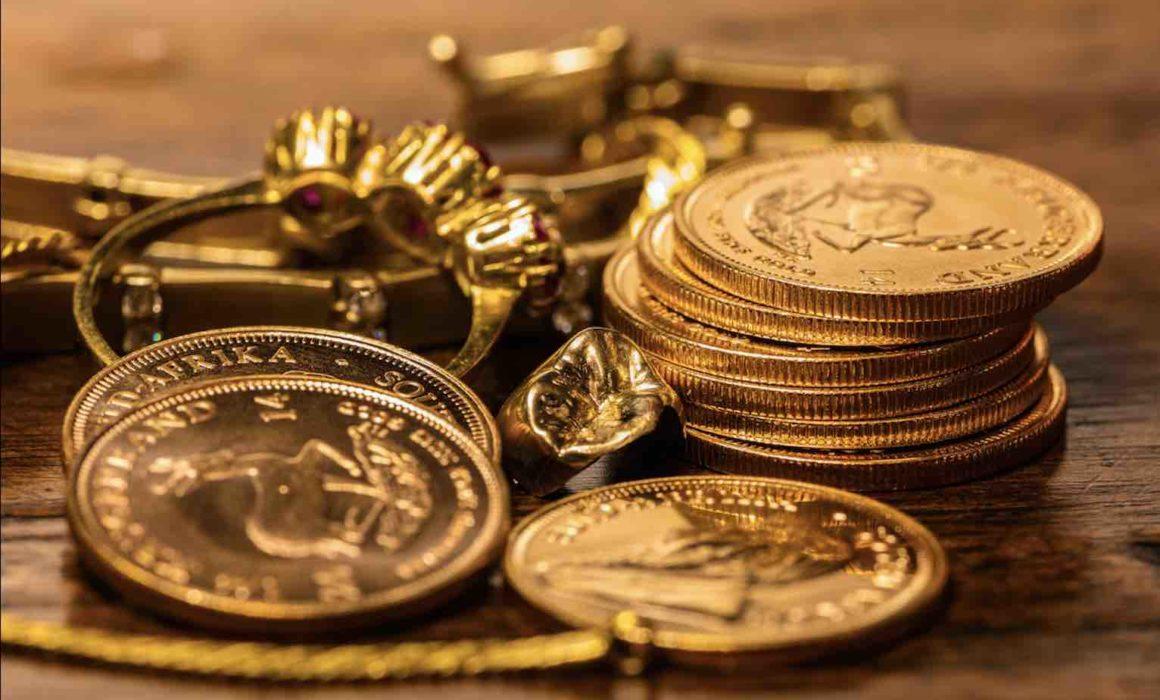 Goldmünzen auf einem Stapel neben Goldschmuck