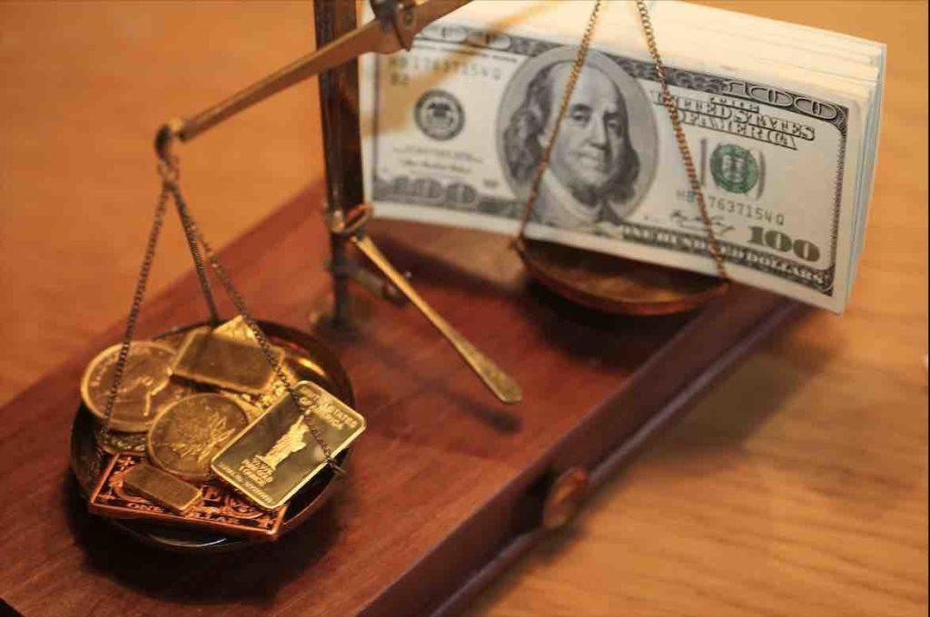 Eine Waage mit Gold und Dollarnoten