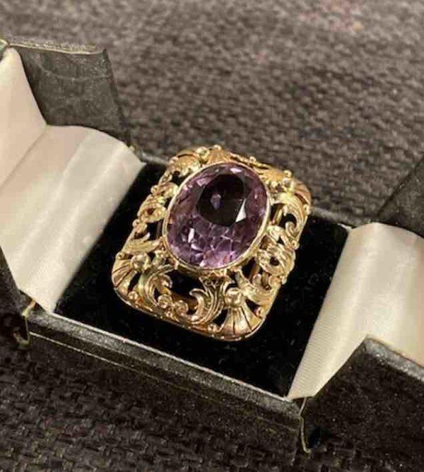 Goldener Ring mit Amethyst in einer Ringschachtel