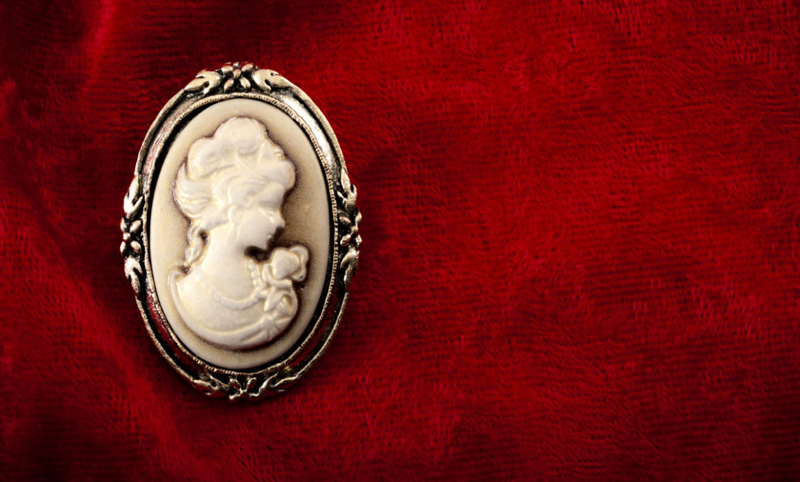Antike Gemme als Brosche auf rotem Hintergrund