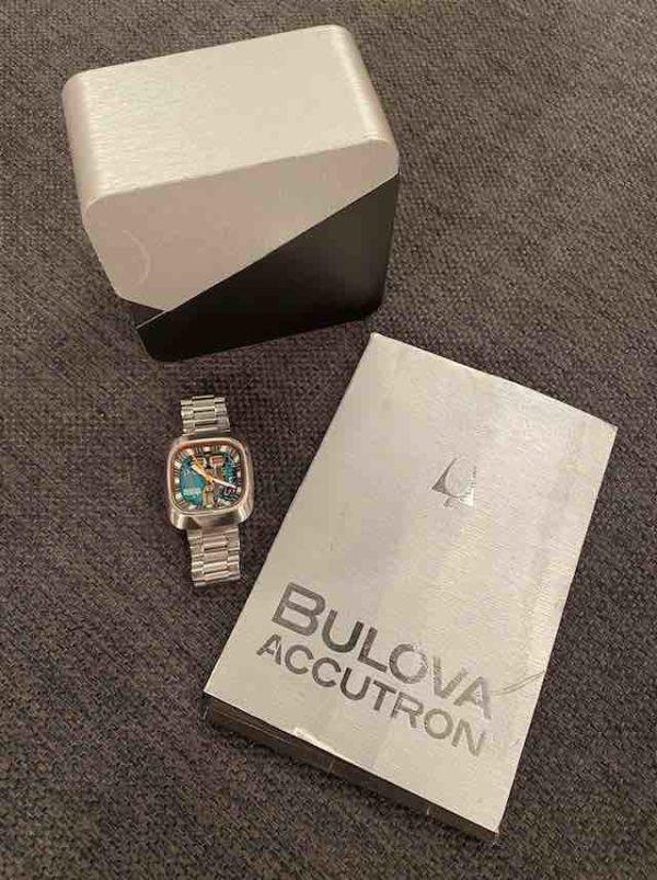Die Bulova Uhr neben der Box und Papieren